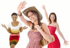 Gruppe junge Frauen, die Hände im Sommerkleid wellenartig bewegen Stockbilder