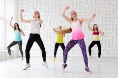 Gruppe junge Frauen, die mit den Armen angehoben beim Haben einer Eignungstanzklasse tanzen stockbilder