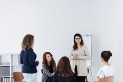 Gruppe junge Frauen, die Sitzen in einem Kreis sprechen Psychologisches St?tzkonzept lizenzfreie stockfotografie