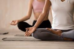 Gruppe junge Frauen, die Yoga, halbe Lotus-Haltung üben stockbilder