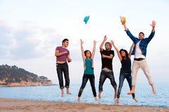 Gruppe junge Freunde, die auf Strand springen. Stockbild