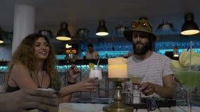 Gruppe junge Freunde, die bei Tisch im Vereinaufenthaltsraum Alkoholcocktails genießend Spaß im Wochenende röstend und habend sit stock video footage