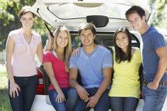 Gruppe junge Freunde, die im Stamm des Autos sitzen Stockbilder