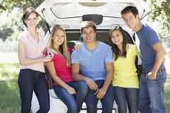 Gruppe junge Freunde, die im Stamm des Autos sitzen Lizenzfreies Stockbild