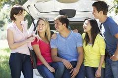 Gruppe junge Freunde, die im Stamm des Autos sitzen Lizenzfreie Stockfotografie