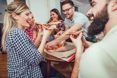 Gruppe junge Freunde, die Pizza essen lizenzfreie stockfotografie