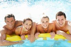 Gruppe junge Freunde, die Spaß im Pool haben Lizenzfreies Stockfoto