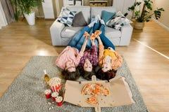 Gruppe junge Freundinnen, die Pizza essen Drei Mädchen, die Pizza beim Lügen auf dem Boden mit den Beinen auf grauem Sofa essen stockfoto