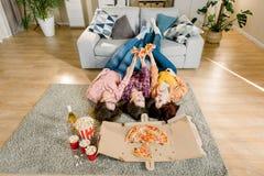 Gruppe junge Freundinnen, die Pizza essen Drei M?dchen, die Pizza beim L?gen auf dem Boden mit den Beinen auf grauem Sofa essen lizenzfreie stockfotografie