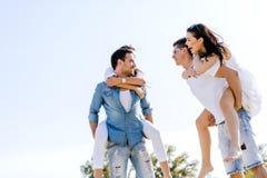 Gruppe junge glücklichen Menschen, die Frauen auf einem sandigen Strand tragen Lizenzfreie Stockbilder