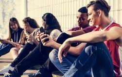 Gruppe junge Jugendlichfreunde, die heraus zusammen unter Verwendung smar kühlen stockfotos