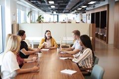 Gruppe junge Kandidaten, die um Tabelle sitzen und auf Aufgabe Geschäfts-am graduierten Einstellungs-Einschätzungs-Tag zusammenar stockfotografie