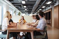 Gruppe junge Kandidaten, die um Tabelle sitzen und auf Aufgabe Geschäfts-am graduierten Einstellungs-Einschätzungs-Tag zusammenar stockbilder