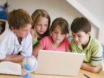 Gruppe junge Kinder, die ihre Heimarbeit tun Stockfotos