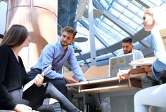 Gruppe junge Leute in der Freizeitkleidung, die am Schreibtisch sitzt und etwas beim PC zusammen betrachten bespricht lizenzfreies stockfoto