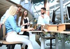 Gruppe junge Leute in der Freizeitkleidung, die am Schreibtisch sitzt und etwas beim PC zusammen betrachten bespricht lizenzfreie stockbilder