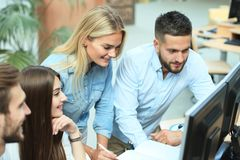 Gruppe junge Leute in der Freizeitkleidung, die am Schreibtisch sitzt und etwas beim PC zusammen betrachten bespricht stockfotografie