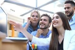 Gruppe junge Leute in der Freizeitkleidung, die am Schreibtisch sitzt und etwas beim PC zusammen betrachten bespricht stockfotos