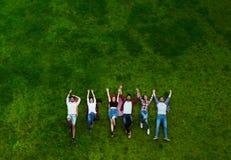 Gruppe junge Leute, die auf das Gras, lächelnd legen stockfotografie