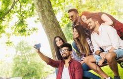 Gruppe junge Leute, die draußen ein selfie auf der Bank, Spaß habend nehmen Lizenzfreie Stockbilder