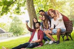 Gruppe junge Leute, die draußen ein selfie auf der Bank, Spaß habend nehmen Stockbilder