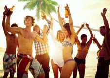 Gruppe junge Leute, die durch den Strand feiern Stockfoto