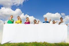 Gruppe junge Leute, die ein großes unbelegtes Papier anhalten Stockbild