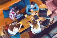 Gruppe junge Leute, die an einem Café, an der Unterhaltung und am Genießen sitzen stockbild