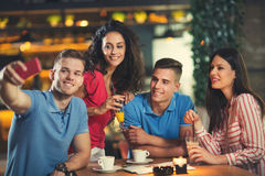 Gruppe junge Leute, die in einem Café sich treffen Lizenzfreie Stockfotografie