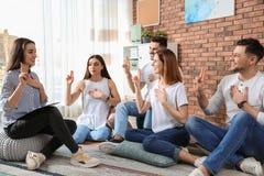 Gruppe junge Leute, die Gebärdensprache lernen stockfotos