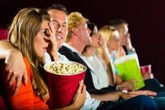 Aufpassender Film der jungen Leute am Kino Lizenzfreie Stockfotos