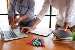 Gruppe junge Leute, die Lektion in der Bibliothek w?hrend des Helfens studierend lernen, Freundausbildung unterrichtend, f?r Pr?f lizenzfreie stockbilder