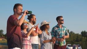 Gruppe junge Leute, die mit Bieren sich entspannen stock footage