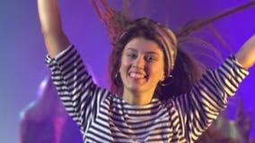 Gruppe junge Leute, die mit den angehobenen Armen im rauchigen Verein tanzen Langsame Bewegung stock video