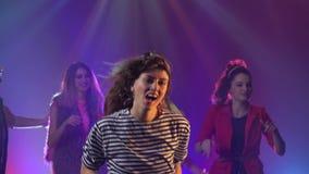 Gruppe junge Leute, die mit den angehobenen Armen zur Musik tanzen stock video