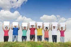 Gruppe junge Leute, die unbelegte Papiere anhalten Lizenzfreie Stockfotografie