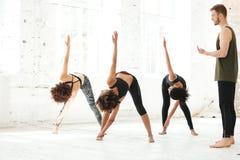 Gruppe junge Leute, die Yoga in der Turnhalle tun Stockbild