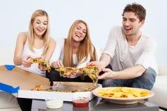 Gruppe junge Leute, die zu Hause Pizza essen stockfotos