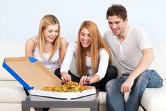 Gruppe junge Leute, die zu Hause Pizza essen Lizenzfreie Stockfotografie