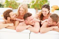 Gruppe junge Leute am Feiertag, der durch Swimmingpool sich entspannt Stockbilder