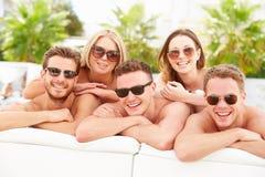 Gruppe junge Leute am Feiertag, der durch Swimmingpool sich entspannt Stockfoto