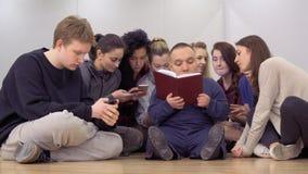 Gruppe junge Leute setzte ihre Telefone und Anfang das Buch lesend beiseite stock video footage