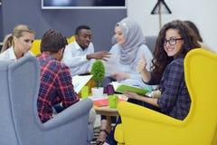 Gruppe junge Leute, Startunternehmer, die an ihrem Risiko in coworking Raum arbeiten stockbild