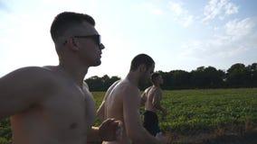 Gruppe junge Männer, die entlang Landstraße über Feld mit Sonnenaufflackern am Hintergrund laufen Profil von den männlichen Athle stockfotografie