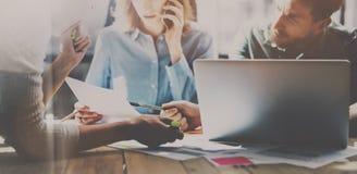 Gruppe junge Mitarbeiter, die im modernen coworking Studio zusammenarbeiten Frau, die Smartphone für die Unterhaltung mit Partner lizenzfreie stockfotos