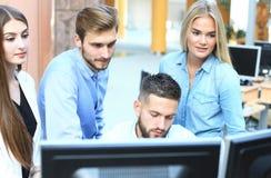 Gruppe junge moderne Leute in der intelligenten Freizeitkleidung, die eine Geistesblitzsitzung bei der Stellung im kreativen Büro stockbild