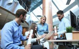 Gruppe junge moderne Leute in der intelligenten Freizeitkleidung, die eine Geistesblitzsitzung bei der Stellung im kreativen Büro stockfoto