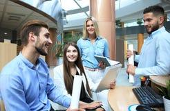 Gruppe junge moderne Leute in der intelligenten Freizeitkleidung, die eine Geistesblitzsitzung bei der Stellung im kreativen Büro lizenzfreies stockbild