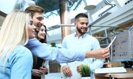 Gruppe junge moderne Leute in der intelligenten Freizeitkleidung, die eine Geistesblitzsitzung bei der Stellung im kreativen Büro lizenzfreie stockfotografie