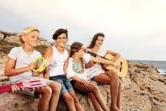 Gruppe junge Musiker, die Spaß auf dem Strand haben stockbild